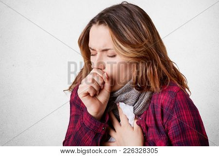 Studio Shot Of Beautiful Young Female Model Has Bad Cough, Uses Tissue, Wears Scarf On Neck, Feels U