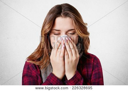 Close Up Shot Of Ill Woman Caught Cold, Feels Sick, Sneezes In Paper Tissue, Has Running Nose, Isola