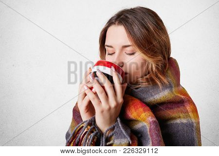 People, Cozy Atmopshere, Season And Heating Concept. Lovely Woman In Warm Plaid Drinks Hot Tea, Warm