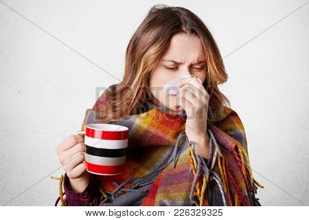 Stressful Young Pretty Woman Sneezes In Napkin, Has Running Nose, Drinks Hot Beverage, Wrapped In Pl