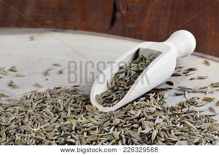 Cumin Seed And Wooden Scoop On Chopping Board (cuminum Cyminum)