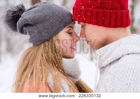 Close-up Of Gilr And Boy Holding Each Other In Knitted Sweaters And Hats During Snowfall