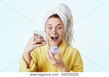 Indoor Shot Of Excited Pleasant Looking Female Model Looks With Surprised Expression At Bottle With