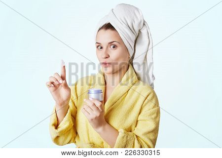 Pretty Young Woman Going To Make Mask On Face After Taking Shower, Holds Bottle With Cream In Hand,
