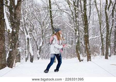Teenage Female Laughing And Having Active Leasure In The Winter Forest
