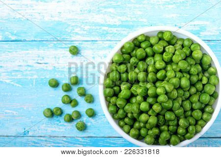 Green Peas.in White Bowl.on Cyan Blue Wooden Rustic Table.top View .copy Space