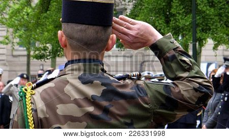 Rear View Of Solider Saluting At Ceremony To Mark Western Allies World War Two Victory Armistice Eur