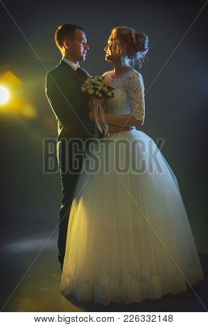 Beautiful Bride In A White Dress And A Young Groom In A Blue Suit In The Studio During A Photoshoot