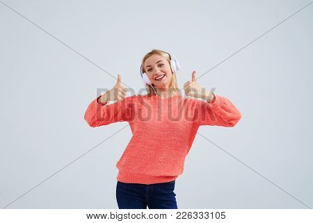 smiley blond in headphones showing thumbs up