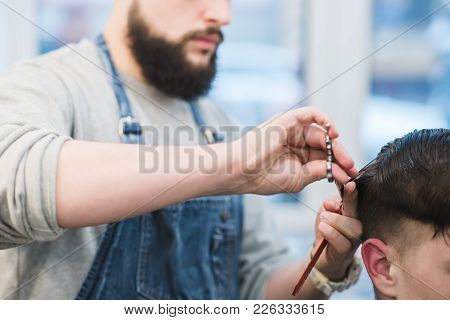 Barber With A Beard Cuts A Customer With Scissors. A Man With A Beard Scissors Cuts His Hair. Men's