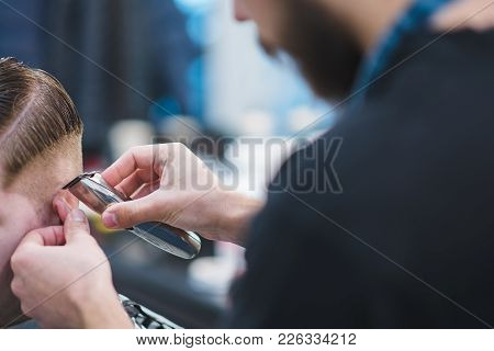 The Hairdresser Creates A Stylish Hairstyle For The Client. Barber With A Beard Cutting A Young Man.