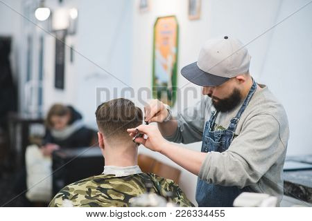 Haircut In Barbershop. The Male Hairdresser With A Beard Makes A Hairstyle To The Client. Barber Cut