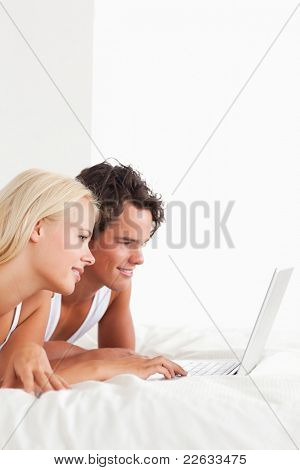 Portrait of a lovely couple using a notebook in their bedroom