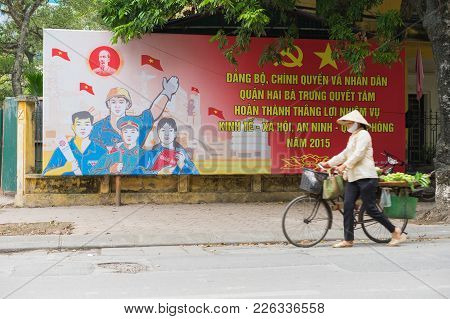 Hanoi, Vietnam - Mar 29, 2015: A Vendor Walking Pass A Communist Propaganda In To Hien Thanh Street