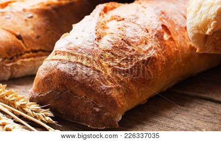 Fresh Baked Bread And Ears Of Wheat On Wooden Background