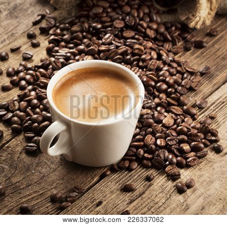 Cup Of Coffee With Coffee Beans On Wooden Background