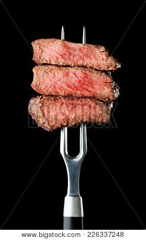 Steak On Fork Isolated On Black Background