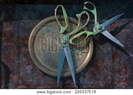 Two Large Scissors, Lying Perpendicular To Each Other, Touching The Handles, On A Copper Yellow Dish