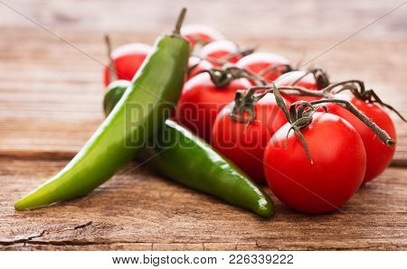 Heap Of Tomatoes With Peppers On Wooden Background
