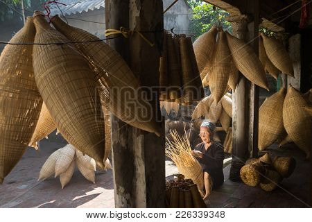 Hung Yen, Vietnam - July 9, 2016: Old House Yard With Many Bamboo Fish Trap And Female Craftsman Mak