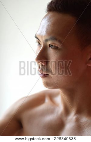 A Side Profile Of A Topless Asian Man