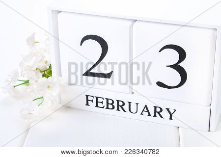White Wooden Calendar With Black 23 February Word With Clock And Plant On White Wood Table