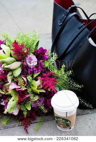 London, Uk - February 12, 2018: Cup Of Starbucks Coffee On The Street With Flowers And Fashion Bag.