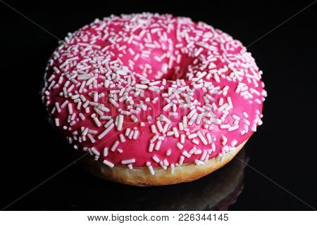 Donut On Black Reflective Studio Background. Isolated Black Shiny Mirror Mirrored Background For Eve