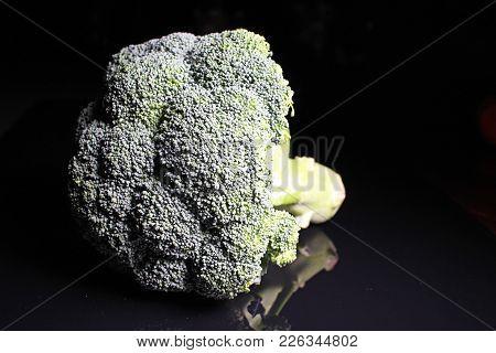 Green Whole Broccoli On Black Reflective Studio Background. Isolated Black Shiny Mirror Mirrored Bac