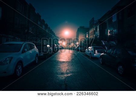 Dark wet city street with cars at night with fog.