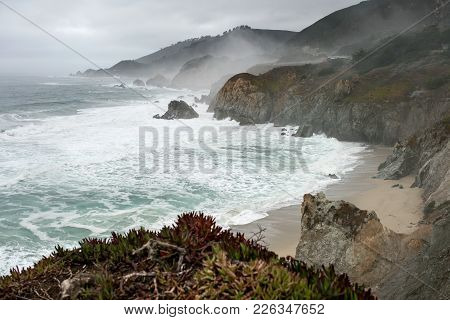 Spectacular Landscape Of The Rocky Shoreline On The Foggy Background Of The Stormy Ocean And The Sky