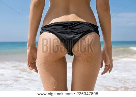 Sexy Girl Stands On The Beach On The Sunny Background Of The Sea And The Blue Sky. She Wears A Black