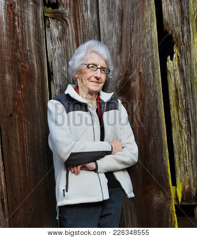 Elderly Woman Leans Against An Old Wooden Barn.  Her Face Is Serene As She Remembers Her Childhood A