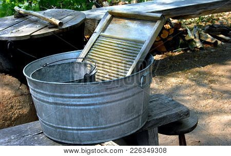 Galvanized Bucket, Black Iron Pot With Wooden Lid, And Wooden Wash Board Sit Side By Side Ready For