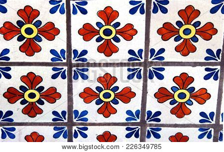 Background Image Show Old Tile Floor With Mosaic Pattern Of Flowers And Fourishes.
