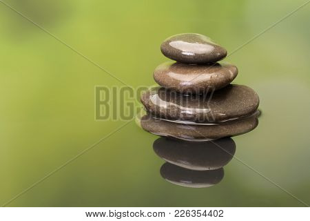 Stacked zen boulders reflected in green water