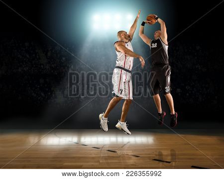 Caucassian Basketball Players in dynamic action with ball in a professional sport game