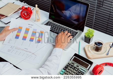 Businessman Analyzing Investment Charts With Laptop Computer On Office Desk Table.close Up.financial