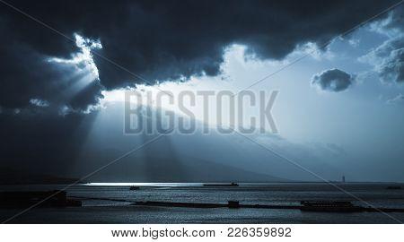 Dark Stormy Clouds And Sunlight, Landscape Background Photo. Cargo Ships Enter Bay Of Izmir, Turkey.