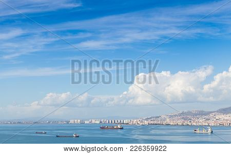Coastal Cityscape With Cargo Ships Under Cloudy Sky. Izmir City, Turkey