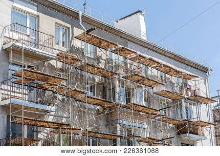 Scaffolding On Urban Apartment Building. Facade Renovation Of Old House.
