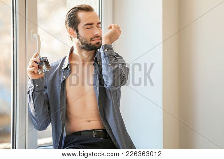 Handsome man in unbuttoned shirt and with bottle of perfume near window
