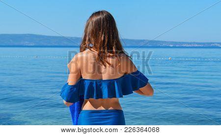 Summer Beach Concept. Pretty Slim Woman In Blue Swimwear Bikini Relaxing On Blue Sea With Sky Backgr