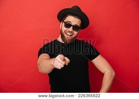 Photo of unshaved cheerful man wearing black sunglasses and hat having fun and pointing finger on camera meaning hey you isolated over red wall