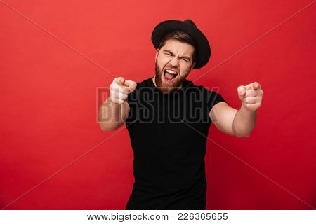 Photo of emotional fancy guy wearing black t-shirt and hat having fun and pointing fingers on camera meaning hey you isolated over red background