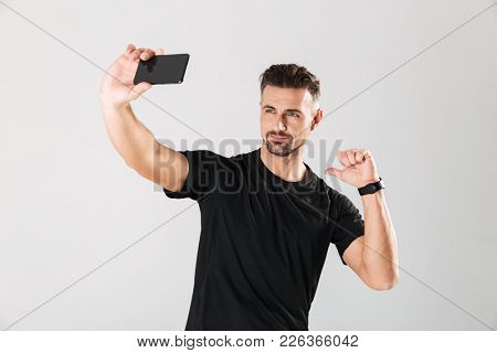 Portrait of a smiling mature sportsman taking a selfie and pointing finger at himself isolated over gray background