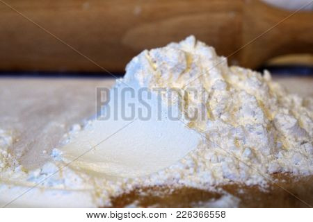 Flour And Rolling Pin On Cutting Wooden Board For Preparation Of Village Food. Ingredients For Cooki