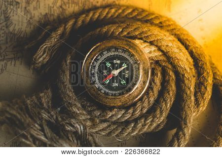 Vintage Old Compass And Rope On The Background Of An Old Map From The Incident Light