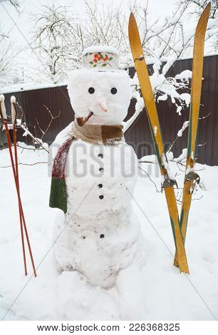Winter Snowman With Scarf And Skiing. Christmas Snowman In Hat With Tobacco Pipe .