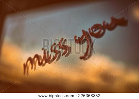 Vintage style conceptual photo of a love from the past, handwritten phrase miss you on the window, grunge background, Valentines day holiday